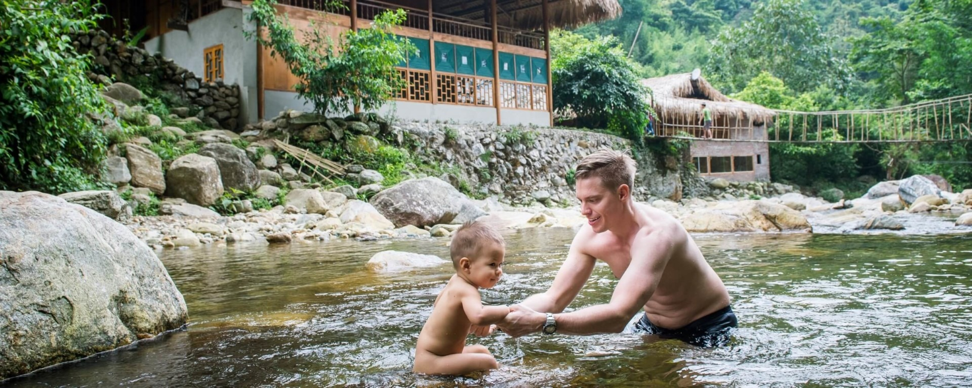 Father and his daugther swimming in jungle river at Topas Riverside lodge