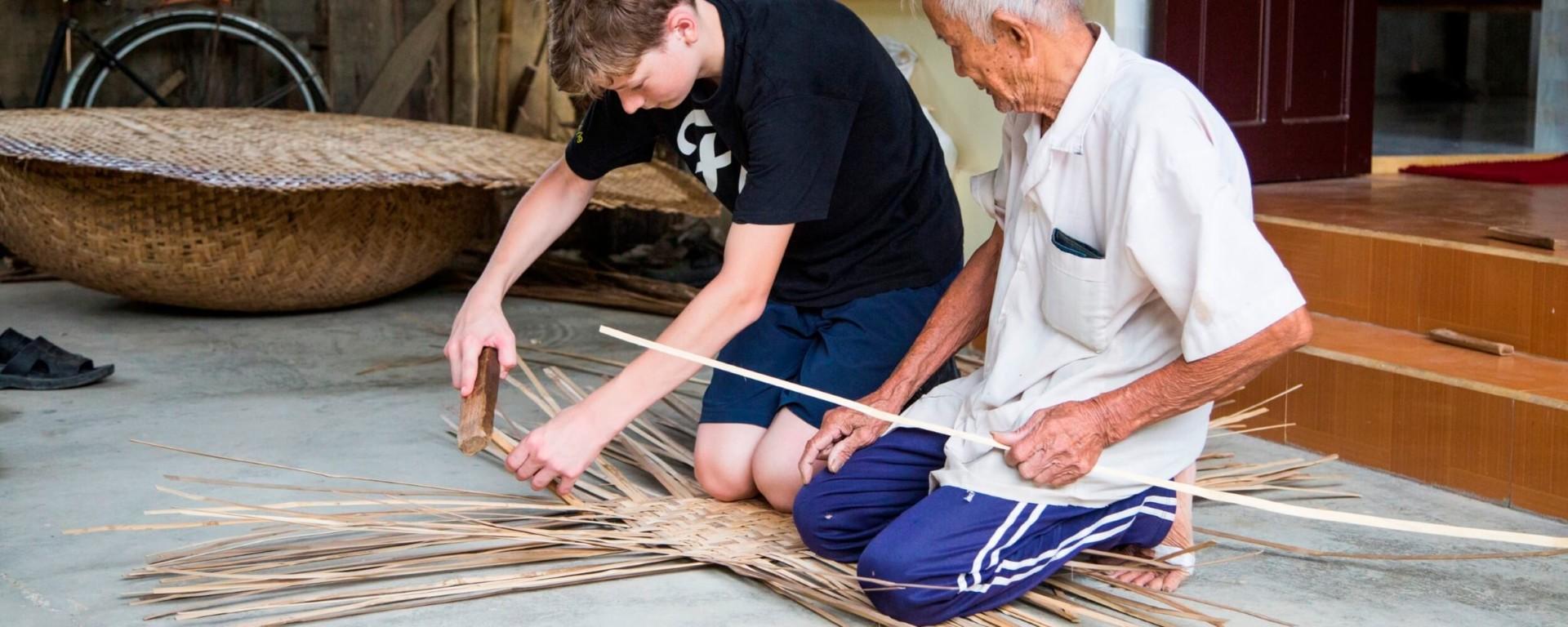 Tourist learnt to do handcraft i Hoi An by an elder Vietnamese man